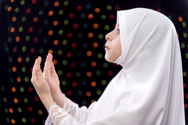 Muslim Girl Duaa on Defocused Night Lights Background