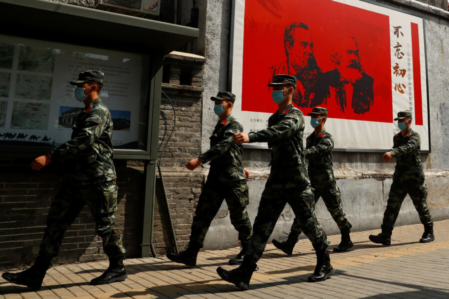 Chińscy żołnierze przechodzą obok portretów niemieckich filozofów Karola Marksa i Fryderyka Engelsa i patrolują ulicę w pobliżu Wielkiej Sali Ludowej w dniu otwarcia Narodowego Kongresu Ludowego (NPC) po wybuchu epidemii koronawirusa (COVID-19), w Pekin, Chiny 22 maja 2020 r. Fot: THOMAS PETER / Reuters / Forum.